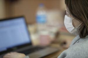 Frau mit Mundschutz am Laptop